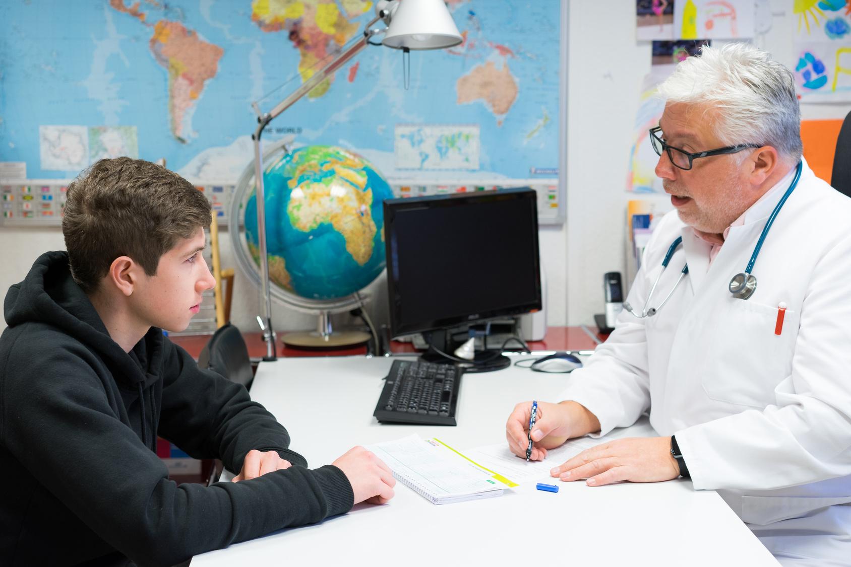 Rheuma: Arzt spricht mit jugendlichem Patienten
