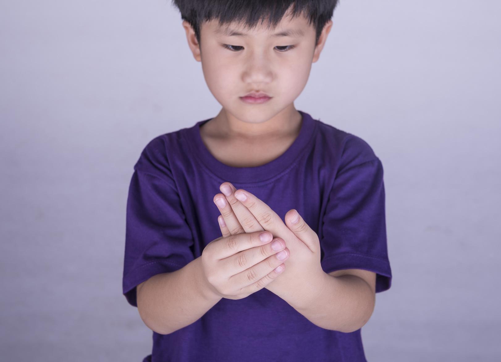 Rheuma: Junge hält seine Hand